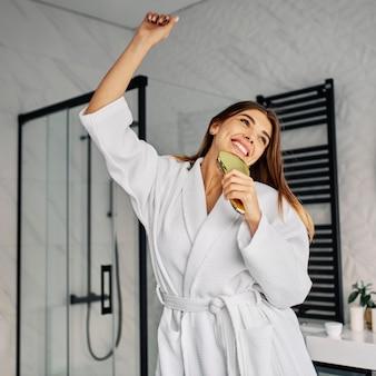 Позитивная молодая женщина в халате