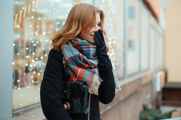 모직 스카프가 달린 가죽 핸드백이 달린 세련된 장갑에 겨울 검은 코트를 입은 긍정적 인 젊은 여성이 꽃으로 장식 된 상점 창 근처에 서서 웃고 있습니다. 좋은 분위기. 귀여운 소녀.