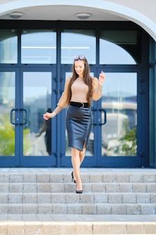 オフィスビルの近くの階段を降りるブラウスと革のスカートでポジティブな若い女性