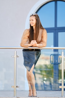 オフィスビルの近くの手すりに寄りかかってブラウスと革のスカートでポジティブな若い女性