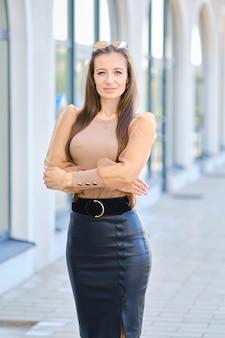 ブラウスと革のスカートのポジティブな若い女性がオフィスビルの近くに立っています