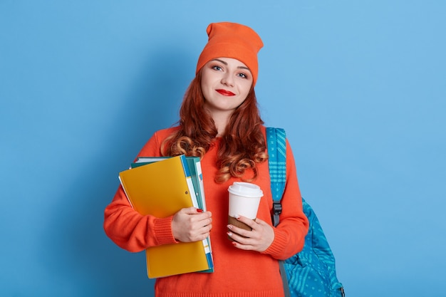 캐주얼 옷에 긍정적 인 젊은 여성, 카푸치노와 일회용 컵을 들고 배낭과 종이 폴더를 운반