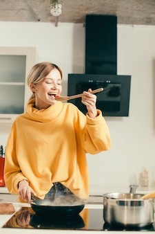 Позитивная молодая женщина в теплом желтом свитере стоит на кухне перед сковородой и улыбается, пробуя помидоры черри с деревянной ложки