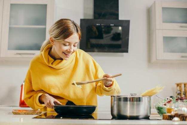 Позитивная молодая женщина в желтом свитере, прислонившись к сковороде и улыбаясь, пробует еду из деревянной ложки
