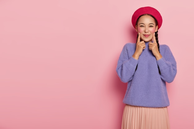 Positive young woman keeps fore fingers on both cheeks, being in high spirit, wears red beret, purple sweater and skirt, stands over pink wall