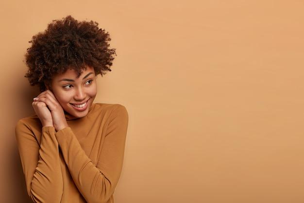 Позитивная молодая женщина держит руки возле лица, задумчиво смотрит в сторону, глубоко думает о приятном, недавно произошедшем