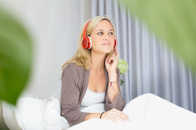 Positive young woman listening music in bed