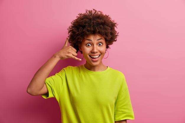 긍정적 인 젊은 여자가 귀 근처에 전화 제스처를 만들고 분홍색 벽에 캐주얼 티셔츠를 입은 사람에게 당신과 대화를 나누고 싶어합니다.