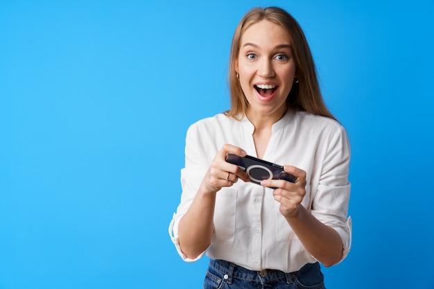 Позитивная молодая женщина играет в игры на смартфоне на синем фоне