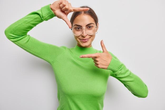 긍정적인 젊은 여성은 완벽한 각도의 관점이나 영감을 검색하여 프레임 제스처가 큰 광학 안경을 착용하고 녹색 터틀넥이 회색 벽 위에 격리된 좋은 샷을 알아냅니다.