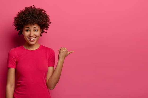ポジティブな若い女性の店員は、顧客が楽屋を見つけるのを助け、販売中の製品を宣伝し、親指を脇に置き、カジュアルなtシャツを着て、嬉しそうに笑い、ピンクの壁に隔離されます。