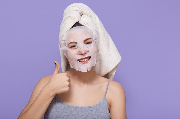 Positive young woman shows her big thumb up while posing with cosmetic mask on her face