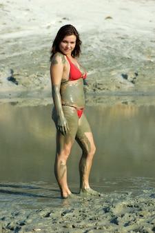 호수에서 치유 진흙으로 얼룩진 긍정적 인 젊은 여성