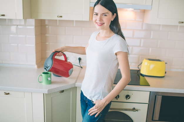 Positive young woman stands in kitchen