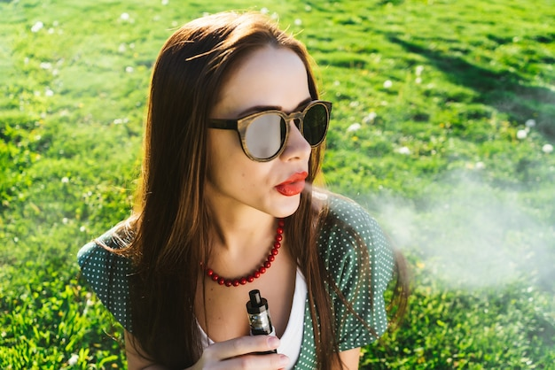 Positive young woman in sunglasses is sitting on the lawn with bright green grass, smoking, thoughtful