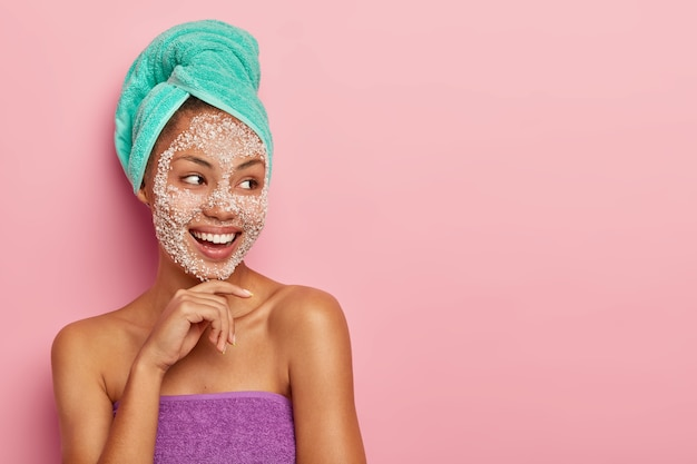 Positive young woman touches gently chin, focused away, has toothy smile, wrapped towel around head and body, enjoys life and beauty treatments