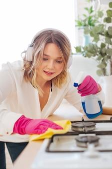 Позитивная молодая женщина, используя очищающее средство во время чистки газовой плиты