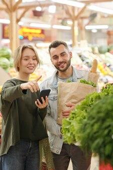 彼らが市場で製品を購入している間、購入し、彼氏に緑を指すためにスマートフォンアプリを使用しているポジティブな若い女性