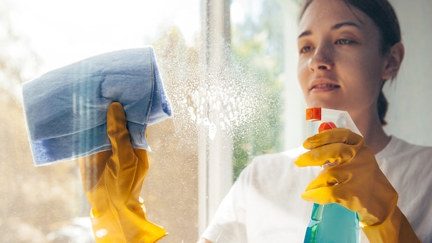 Positive young woman washing windows in yellow gloves