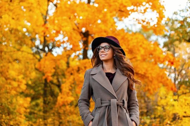 トレンディなメガネでスタイリッシュなコートを着たエレガントな帽子をかぶった巻き毛の美しい笑顔のポジティブな若い女性は、秋の公園で残りを楽しんでいます。かなり幸せな流行に敏感な女の子は屋外でリラックスしています。