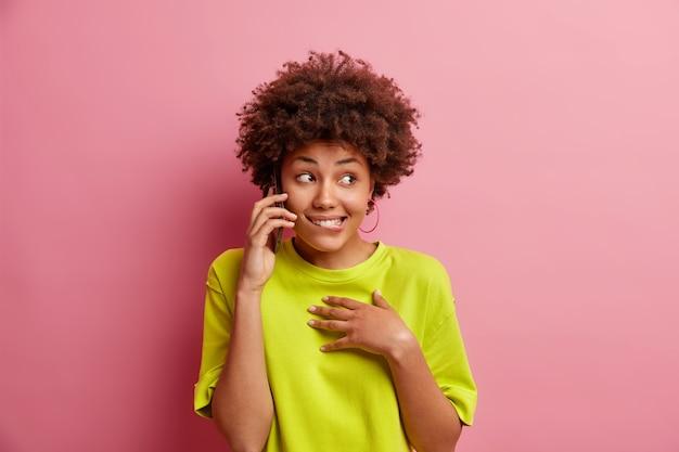 携帯電話で巻き毛の話をしているポジティブな若い女性は唇をかじり、ピンクの壁に隔離されたカジュアルなtシャツを着て嬉しいと感じます友人が答えるまで待ちます