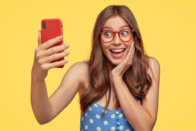黄色の壁に対してポーズをとって眼鏡をかけてポジティブな若い女性