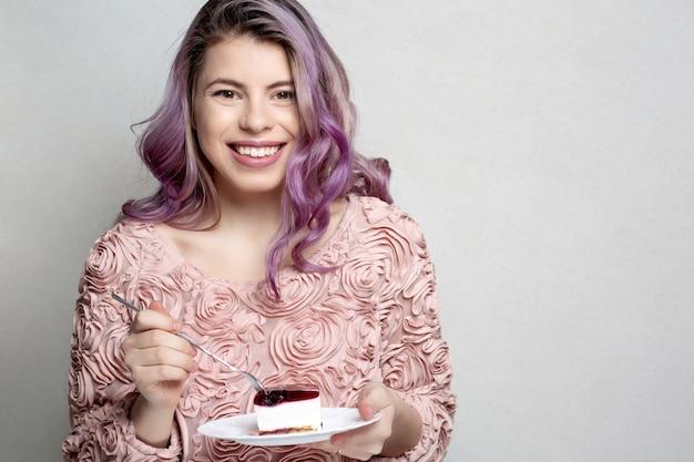灰色の背景の上においしいチーズケーキを保持している紫色の巻き毛を持つポジティブな若い女性。テキスト用のスペース