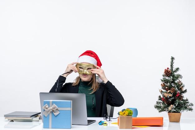 Positivo giovane donna con cappello di babbo natale e indossa una maschera seduto a un tavolo con un albero di natale e un regalo su di esso in ufficio su sfondo bianco
