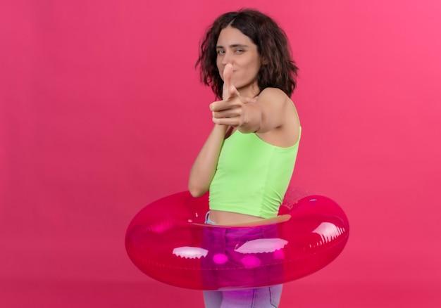 Una giovane donna positiva con i capelli corti in crop top verde sorridendo e indicando la telecamera su uno sfondo rosa
