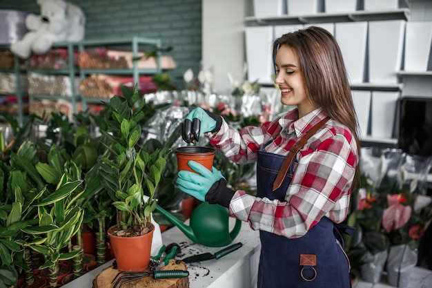 Positive young woman working in flower center