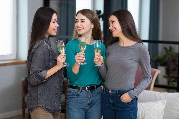 Positive young women celebrating with champagne
