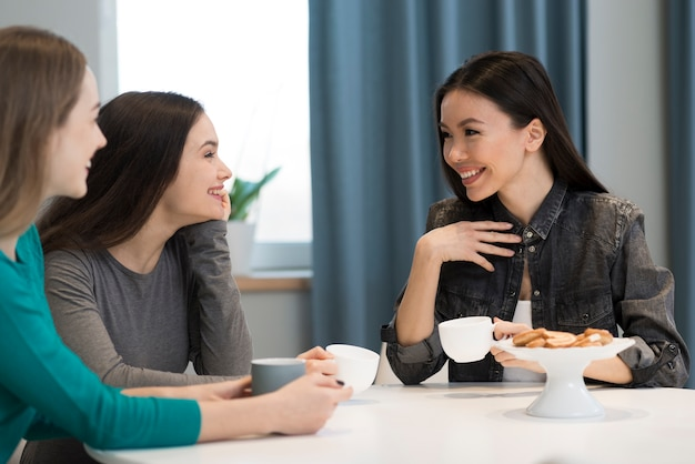 Positive young women having coffee and smiling