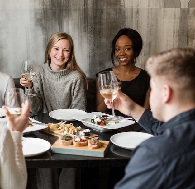 Positive young women smiling at dinner party