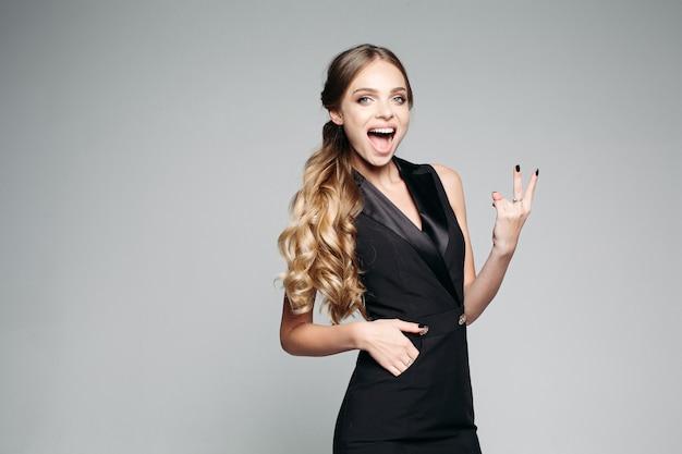 Позитивность и эмоциональная девушка показывает знак мира пальцами