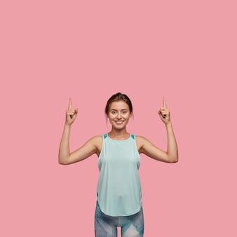Positve 쾌활한 여성은 기뻐하며 두 검지 손가락을 위로 향하게하고 캐주얼 조끼와 레깅스를 입고 분홍색 벽에 모델을 둡니다. 행복 한 백인 여자는 위층 방향을 보여줍니다.