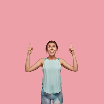 Positve european woman with glad expression, points with both index fingers upwards, dressed in casual vest and leggings, models over pink wall. advertisement concept. look at ceiling!