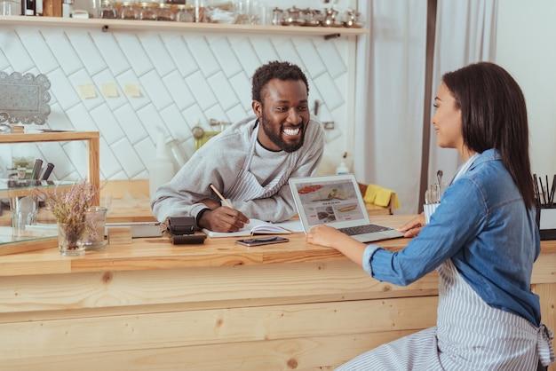 可能な改善。男性の同僚の前に座って、カフェのウェブサイトで可能な改善について彼と話している美しい若い女性のバリスタ
