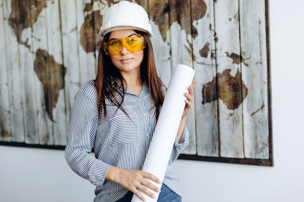 白いヘルメットと図面で黄色のメガネでpossing若い笑顔の女性