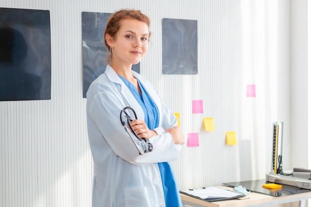 女医possingの笑みを浮かべて、病室で聴診器を着ています。