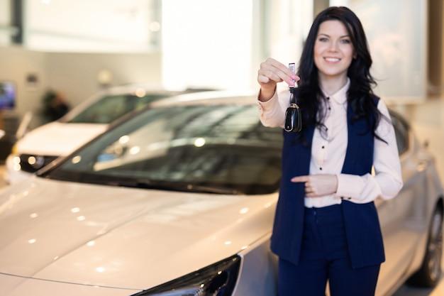 車のディーラーで彼女の新しい車の近くのキーを持つpossing幸せな女性バイヤー