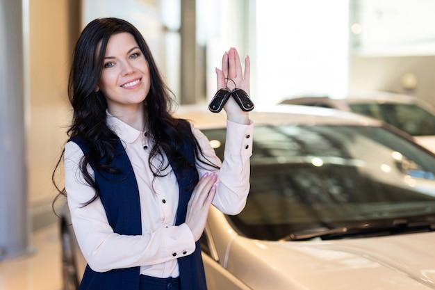 Счастливый покупатель женщины possing с ключами около ее нового корабля в автосалоне
