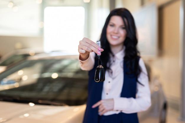カーディーラーで彼女の新しい車の近くのキーを持つpossing幸せな女性バイヤー