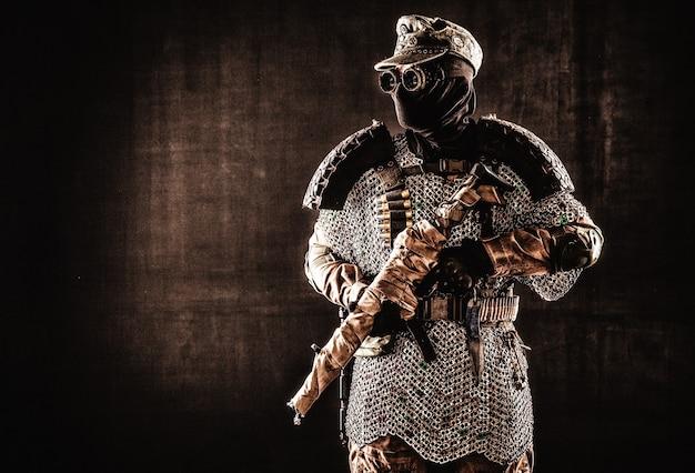 Постапокалиптический солдат в черной маске и очках, шерстяной полевой фуражке и доспехах ручной работы из автомобильных шин и кольчуги, стоящий по стойке смирно с автоматом на плече, студийная съемка на черном фоне