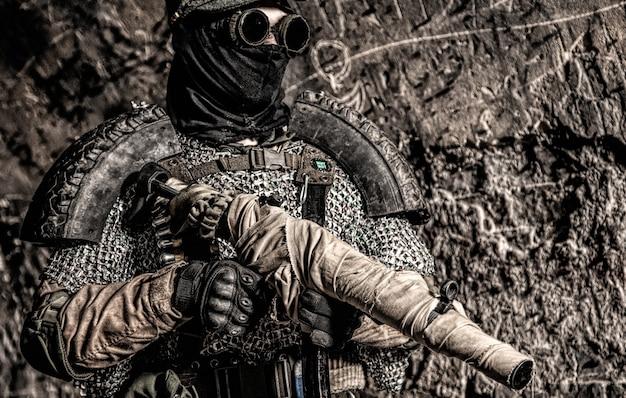 Постапокалиптический выживший, солдат третьей мировой войны, партизан или преследователь глобального ядерного конфликта, в военной фуражке и самодельной броне, стреляет из пистолета-пулемета, завернутого в заброшенный бункер или шахту