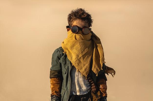 砂漠の荒れ地で屋外の黙示録的な戦士の少年