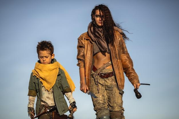 終末論的な女性と少年が屋外で武器を持って勇敢に歩いていることを投稿してください。灰色の空と死んだ