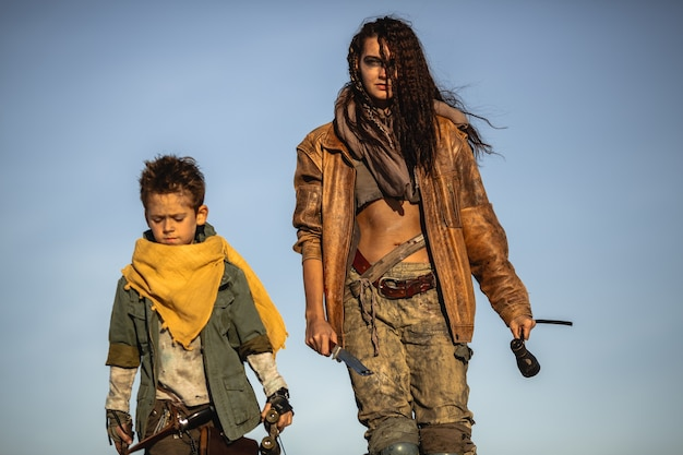 Post apocalyptic woman and boy heroically walking with weapons outdoors. gray sky and dead