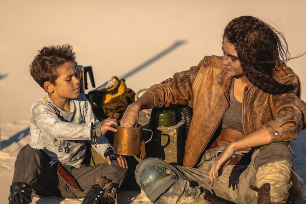 Post apocalyptic woman and boy sitting in the camp outdoors. dead wasteland and some junk on the