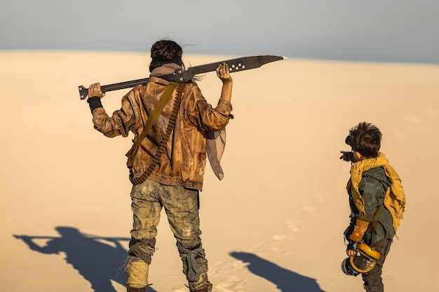 Post apocalyptic woman and boy walking with weapons outdoors. dead wasteland on the background