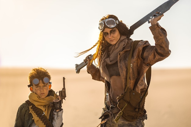 Post-apocalyptic woman and boy with weapons outdoors. desert and dead wasteland on the background